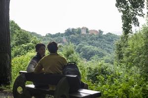 Wanderer bei einer Rast mit Blick auf die Burg Schaumburg